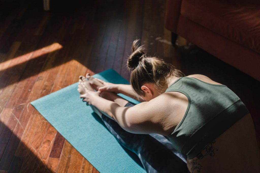 mat pilates exercises - woman stretching on mat on floor